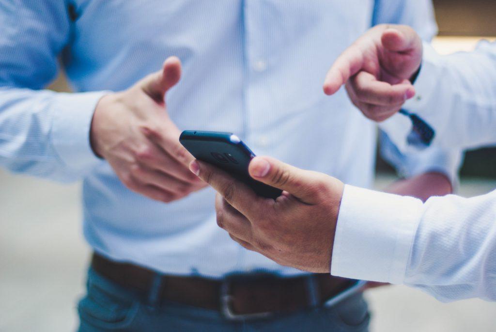 Person hält schwarzes iPhone mit WhatsApp Pay drauf